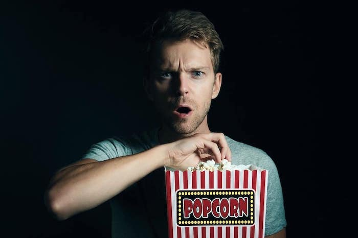 A man eating popcorn and watching a movie he purchased from That Movie Site after getting huge digital movie deals.